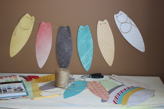 I bought a book of craft paper at Michael's craft store. Then, I drew a picture of a surf board on card stock, cut it out, and traced it onto each patterned piece of paper. Next, I punched two holes into the top of each surfboard. Lastly, I weaved twine through each piece.